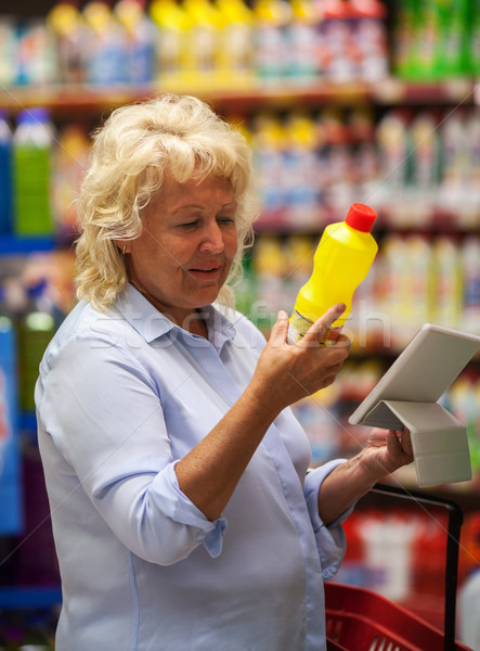 Senior woman with pad reading the detergent label Stock photo © d13