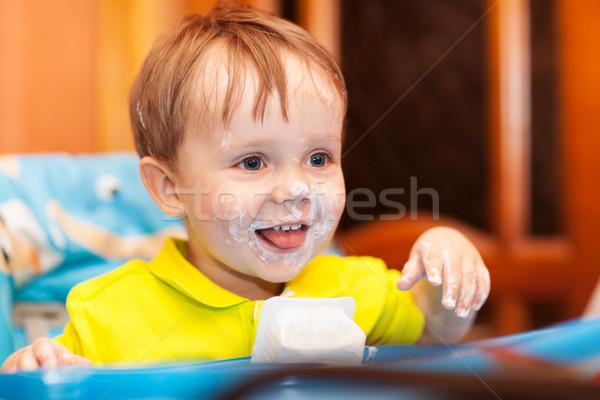 Happy child dirty with cream yoghurt Stock photo © d13