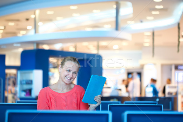 Woman sitting in a waiting room reading tablet Stock photo © d13