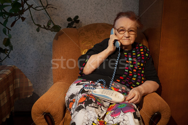 Elderly woman talking on the home phone Stock photo © d13