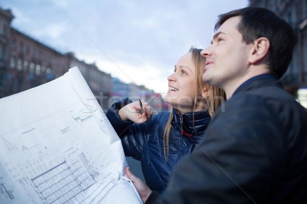 Couple holding blueprints admiring building Stock photo © d13