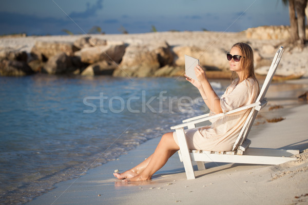 Woman with pad relaxing in chaise-lounge on the beach Stock photo © d13
