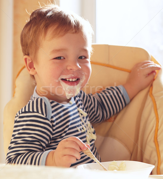 Two year old boy smiles and eating porridge. Stock photo © d13
