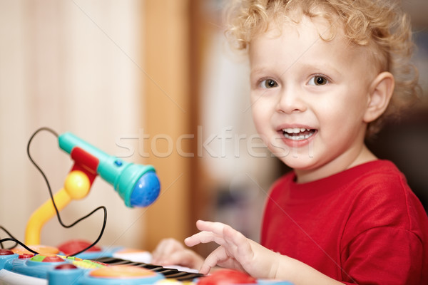 Adorable little boy playing with a toy microphone Stock photo © d13