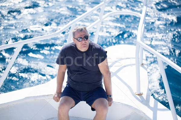 Man sitting on the prow of a boat Stock photo © d13