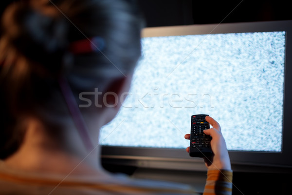 Woman with remote control in front of TV set Stock photo © d13