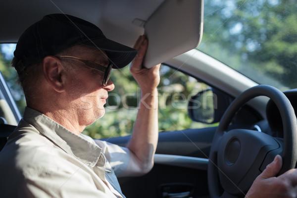 Senior driver hiding from the sun Stock photo © d13