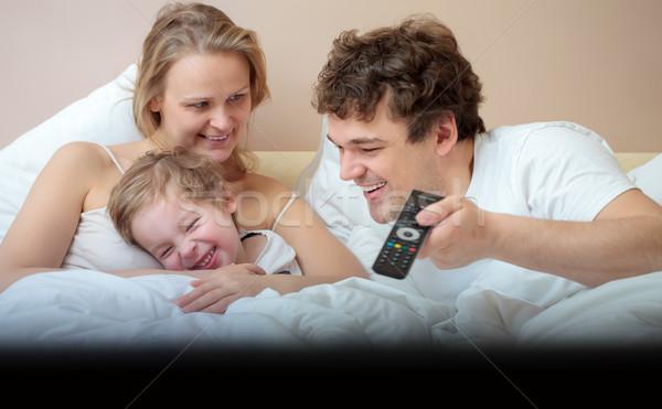 Szczęśliwą rodzinę bed oglądanie telewizji młodych syn śmiechem Zdjęcia stock © d13