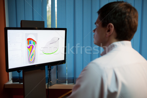 Orthopaedist at work with digital footstep model Stock photo © d13