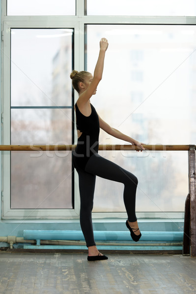 Young ballet dancer exercising at the barre in studio Stock photo © d13