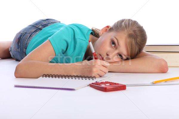 Primary school girl doing math homework on floor Stock photo © darrinhenry