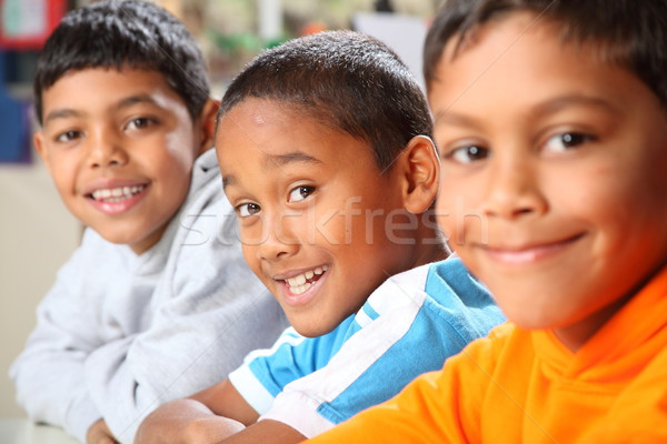 Row of three smiling young school boys sitting in class Stock photo © darrinhenry