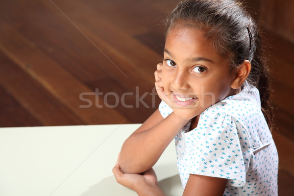 Smiling young school girl 10 sitting to her classroom desk Stock photo © darrinhenry