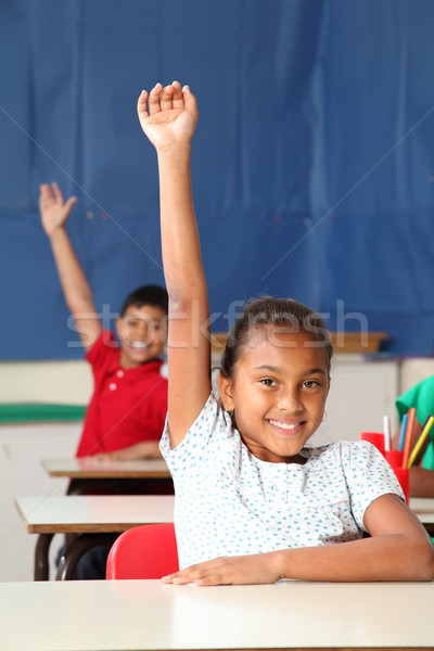 Two smiling young school children arms raised in class Stock photo © darrinhenry