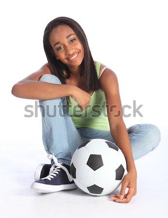Happy teenage girl football player sits with ball Stock photo © darrinhenry