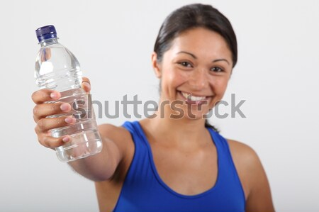 Girl holding out sharply focused bottled water Stock photo © darrinhenry