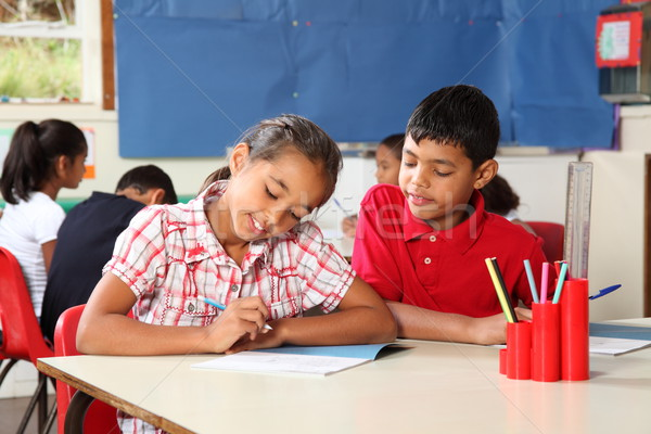 School children boy and girl concentrating on lesson in classroom Stock photo © darrinhenry