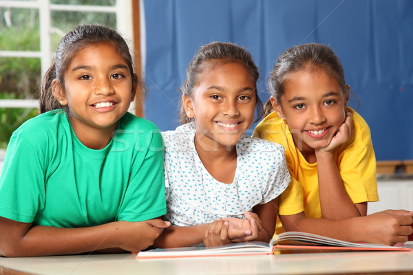 Three happy young school girls reading a book in class Stock photo © darrinhenry