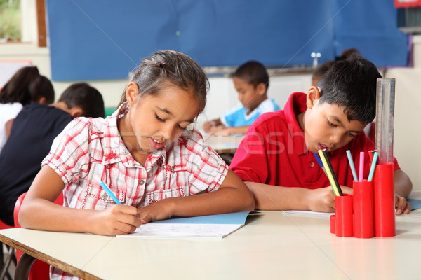 School children boy and girl in classroom concentrating on lesson Stock photo © darrinhenry