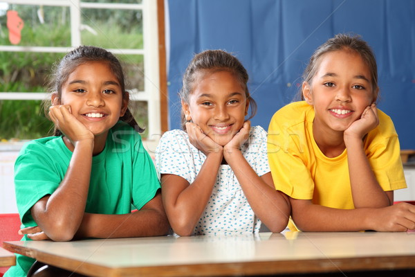 Three happy young school girls leaning on desk in class Stock photo © darrinhenry