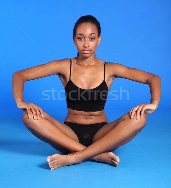 Athletic african fitness woman sits cross legged Stock photo © darrinhenry