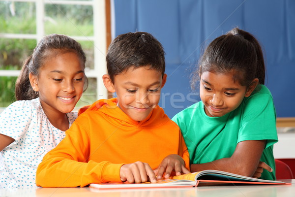 Three primary school children in class reading and learning together Stock photo © darrinhenry