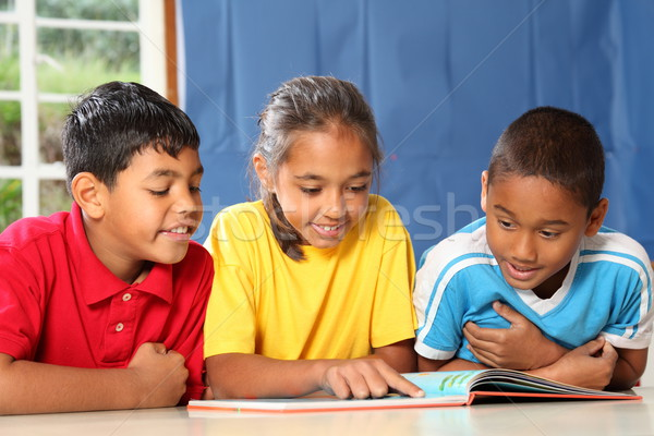Learning together three happy young school kids reading in class Stock photo © darrinhenry
