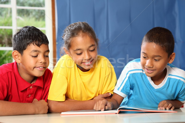 Three primary school friends reading and learning together in class Stock photo © darrinhenry