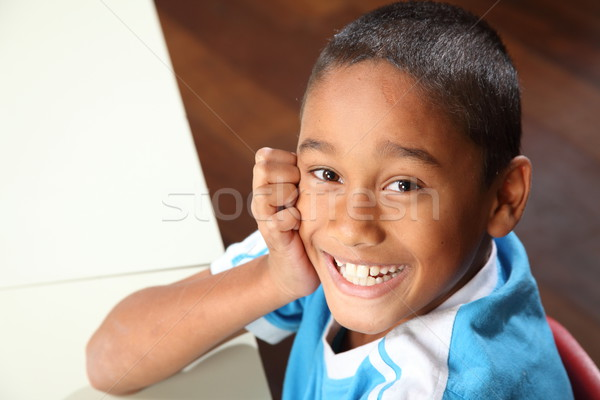 Laughing young school boy 9 sitting to his classroom desk Stock photo © darrinhenry