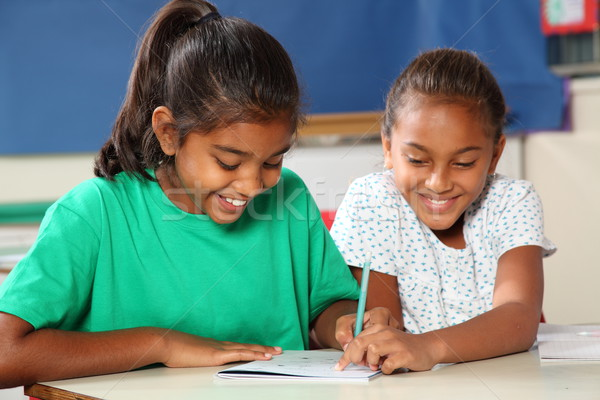 Stock photo: Two cheerful school girls in classroom helping each other learn