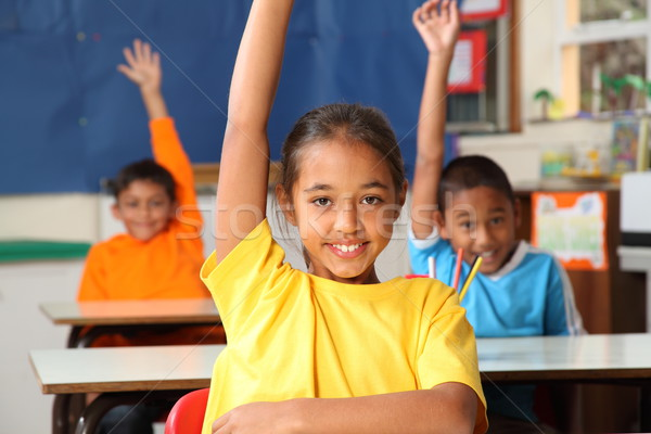 Three primary school children hands raised in class Stock photo © darrinhenry