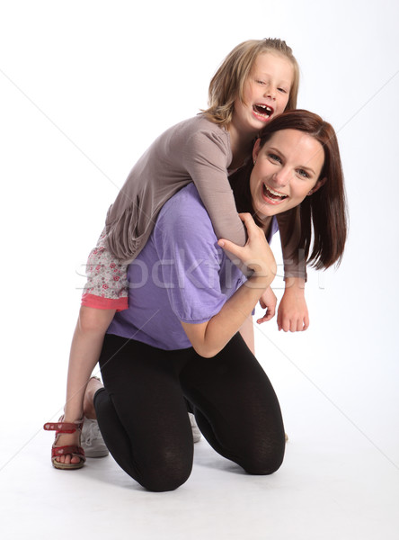 Happy mother giving daughter fun piggy back ride Stock photo © darrinhenry