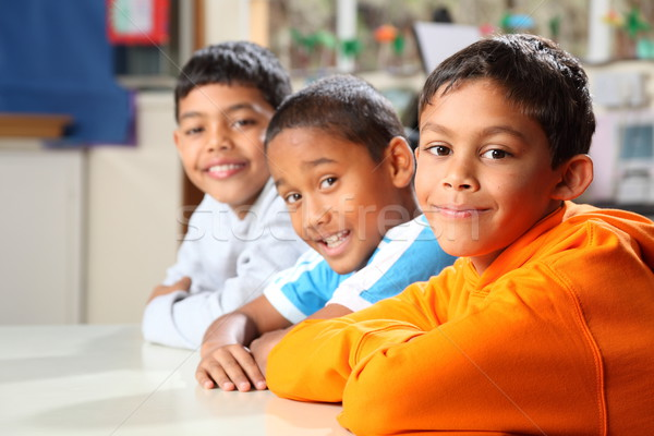 Three smiling primary school friends sitting together in class Stock photo © darrinhenry