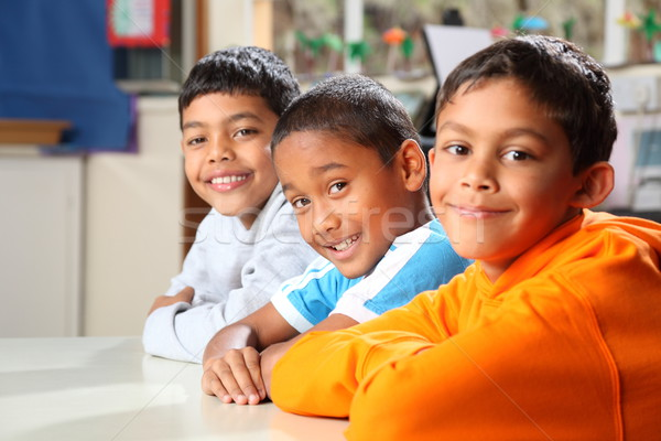 Three smiling primary school boys sitting patiently in class Stock photo © darrinhenry