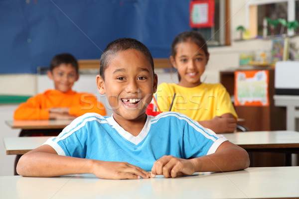 Cheerful primary school children sitting to desks in classroom Stock photo © darrinhenry