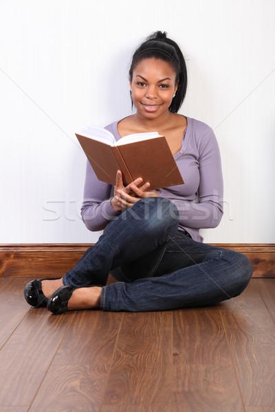 Beautiful african american girl reading a book Stock photo © darrinhenry