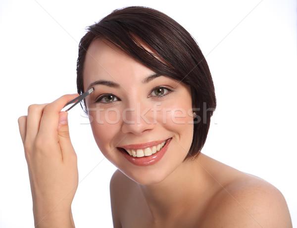 Beautiful woman plucking eyebrow with tweezers Stock photo © darrinhenry