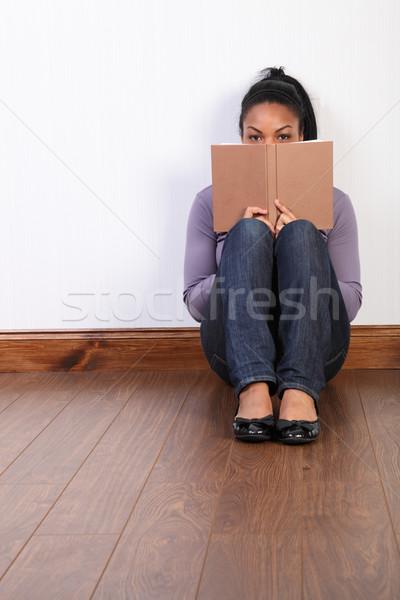 Black girl sitting on floor at home reading book Stock photo © darrinhenry