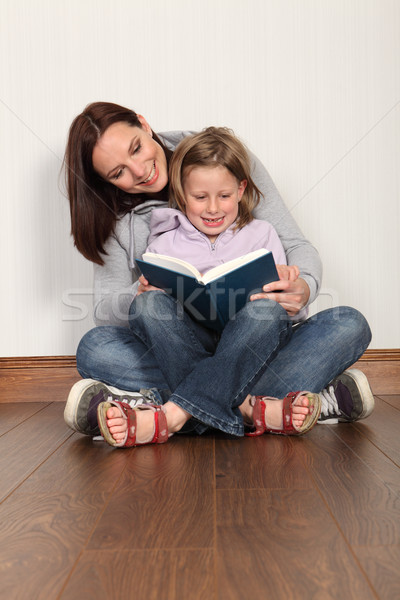 Stock photo: Mother teaching daughter to read home education