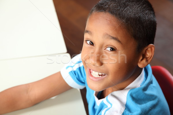 Smiling young school boy 9 sitting to his classroom desk Stock photo © darrinhenry