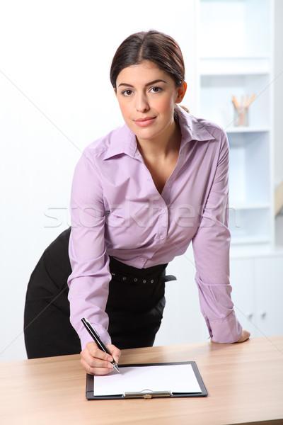Beautiful businesswoman signing document at work Stock photo © darrinhenry