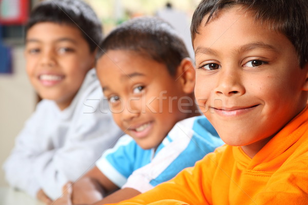 Three smiling young primary school boys sitting in class Stock photo © darrinhenry