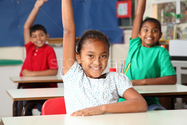 Three smiling young school children arms raised in class Stock photo © darrinhenry
