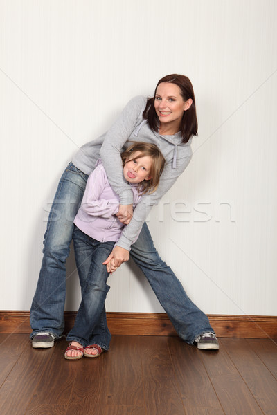 Stock photo: Embrace of family love and fun for mother daughter