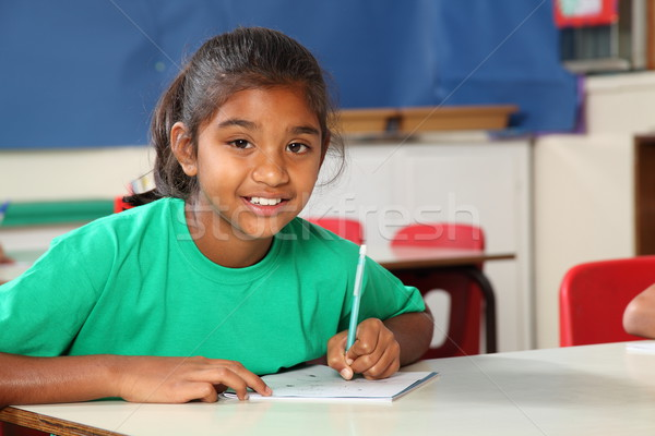 Young school girl 9 writing at her classroom desk Stock photo © darrinhenry