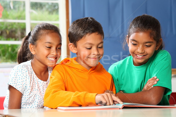 Three primary school children reading and learning together in class Stock photo © darrinhenry