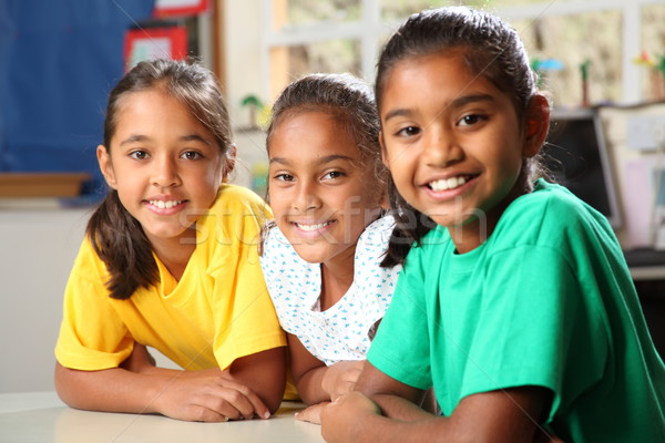 Three smiling young primary school girls sitting in class Stock photo © darrinhenry