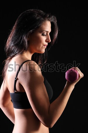 Bicep curl by beautiful young fitness woman Stock photo © darrinhenry