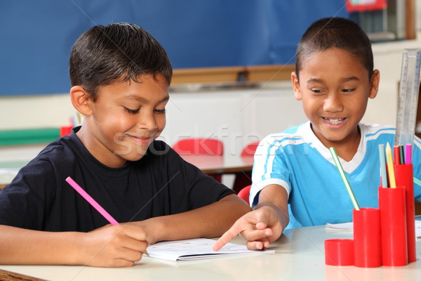 Two schoolboys helping each other learn in class during lessons Stock photo © darrinhenry