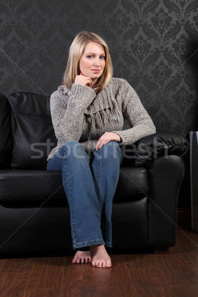 Beautiful blonde woman home sits on leather settee Stock photo © darrinhenry